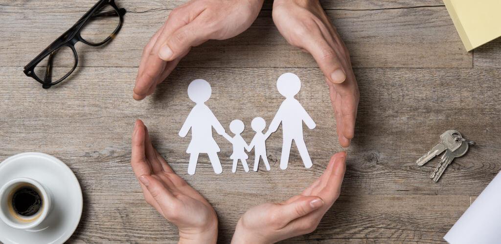 家族のイラストを包み込む二人の手